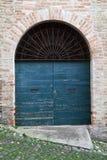 Blaue Holztür mit Bogen in der alten Backsteinmauer Stockbilder