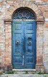 Blaue Holztür mit Bogen in der alten Backsteinmauer Stockfotos