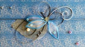 Blaue horizontale handgemachte Grußdekoration mit glänzenden Perlen, Stickerei, silbernem Thread in der Form der Blume und Schmet Stockfotos