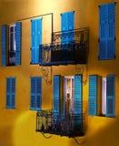 Blaue Jalousien auf einer alten gelben Wand Stockfoto