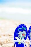 Blaue Jelly Sandals mit der Libelle, die auf den Sand legt Meer auf Lizenzfreie Stockfotos