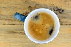 Blaue Kaffeetasse auf altem Holz mit Text Stockfotografie