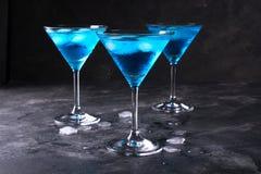 Blaue kalte Cocktails trinken mit Eiswürfeln auf einem dunklen Hintergrund Stockbild