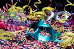 Blaue Karnevalsmaske über Konfettis und mehrfarbigen Ausläufern lizenzfreies stockfoto