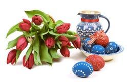 Blaue Keramik mit Ostereiern und roten Tulpen auf Weiß Stockfotografie