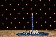 Blaue Kerze und Perlen des neuen Jahres mit Nr. 2018 auf einem hölzernen Vorsprung Lizenzfreie Stockfotos