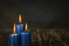Blaue Kerzen des Lit drei auf hölzernem Zähler Stockfotos