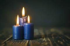 Blaue Kerzen des Lit drei auf hölzernem Zähler Stockbild