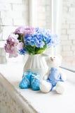 Blaue Kind-` s Schuhe mit einem Spielzeughasen und einem Blumenstrauß von blauen Blumen auf dem Fensterbrett Stockfoto