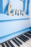 Blaue Klaviernahaufnahme mit Schwarzweiss-Schlüsseln mit Text Liebe ist Stockfotos