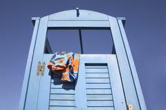 Blaue Kleidkabine am Strand mit einer Schwimmenklage, die heraus hängt Stockfotos