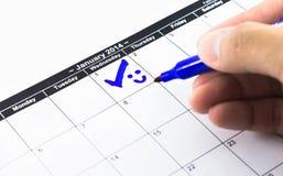 Blaue Kontrolle mit Lächeln. Kennzeichen auf dem Kalender an am 1. Januar 2014 Stockfotografie