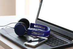 Blaue Kopfhörer und ein intelligenter Telefonrest auf einer Laptop-Computer mit Beschneidungspfad auf dem PC-Schirm- und -kopienr stockfotografie