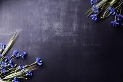Blaue Kornblumen und Roggen auf alter Tafel von der Spitze Stockfotografie