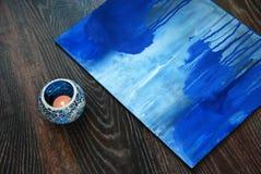 Blaue Malereibürste und -kerze im Kerzenständer Stockfotos