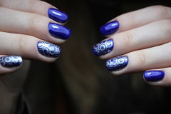 Blaue Maniküre mit silbernem Muster stockbilder