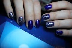 Blaue Maniküre mit silbernem Muster lizenzfreies stockfoto