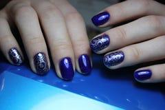 Blaue Maniküre mit silbernem Muster stockfotos