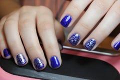 Blaue Maniküre mit silbernem Muster lizenzfreie stockfotos