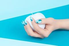 Blaue Nägel und Apple in der Hand stockbild