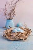 Blaue Ostereier im Nest auf hölzernem Hintergrund Lizenzfreie Stockbilder