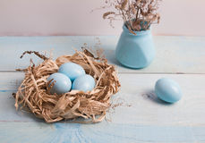 Blaue Ostereier im Nest auf hölzernem Hintergrund Stockbild