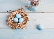 Blaue Ostereier im Nest auf hölzernem Hintergrund stockbilder