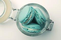 Blaue Pastellmakronen im Glasgefäß Stockfotos