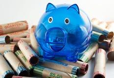 Blaue Piggy Querneigung mit Münzen-Verpackungen Stockfotos