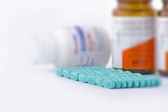 Blaue Pillen mit Medizinflaschen stockfotos