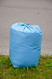 Blaue Plastikabfalltasche auf Straße Stockbild