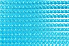 Blaue Plastikspiralenstöcke auf blauem Hintergrund Stockfotos