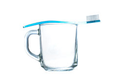 Blaue Plastikzahnbürste steht auf einem transparenten Glasbecher auf Weiß still Lizenzfreies Stockbild