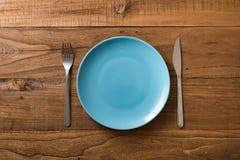 Blaue Platte auf braunem hölzernem Hintergrund mit Geräten Stockbilder