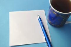 Blaue Porzellanporzellanschale mit blauem Stift und Bleistiften, weiße Anmerkungskarte und blauer Hintergrund Stockbild