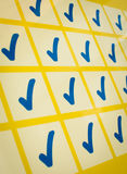 Blaue Prüfzeichen im gelben Gitter Stockfotografie
