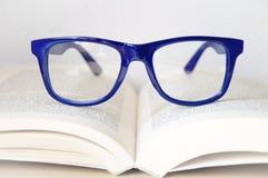 Blaue Rahmenaugengläser und -offenes Buch Stockbilder