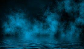 Blaue rollende Wogen des Rauchnebels vom Trockeneis über dem unteren Licht mit Reflexion im Wasser lizenzfreie stockfotos
