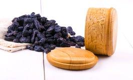 Blaue Rosinen zerstreuten auf Leinwand in einer hölzernen Schale auf einem weißen Holz Lizenzfreies Stockbild
