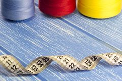 Blaue, rote und gelbe Threads, Zentimeterband, hölzerner Hintergrund, Dressmaking lizenzfreie stockbilder