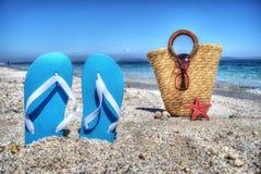 Blaue Sandalen und Stroh bauschen sich durch das Ufer Lizenzfreies Stockfoto