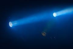 Blaue Scheinwerferlichter mit Strahlen in der rauchigen Dunkelheit lizenzfreie stockbilder
