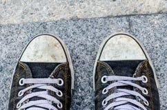 Blaue schmutzige Turnschuhe auf Straße Lizenzfreie Stockfotos