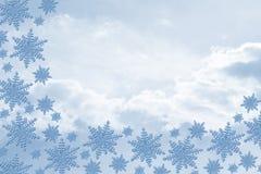 Blaue Schneeflocken mit Wolken-Hintergrund Stockbild