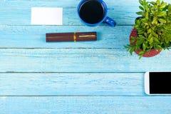 Blaue Schreibtischtabelle mit Computer, Stift und ein Tasse Kaffee, Los Sachen Draufsicht mit Kopienraum Lizenzfreies Stockfoto
