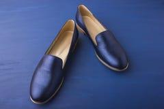 Blaue Schuhe auf einem blauen Hintergrund Stockfotos