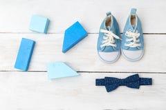 Blaue Schuhe des Babys und blaue hölzerne Spielwaren auf hölzernem Hintergrund f Stockfotos