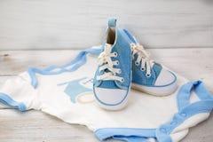 Blaue Schuhe für Babykleidung und für einen Jungen auf einer weißen hölzernen Rückseite Lizenzfreie Stockfotos