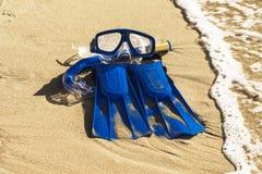 Blaue Schwimmenflipper, Maske, Schnorchel für die Brandung, die auf dem sandigen Strand laing ist Seeshell mit Ozean auf Hintergr lizenzfreie stockfotografie