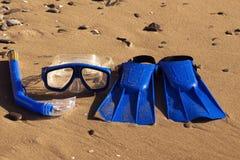 Blaue Schwimmenflipper, Maske, Schnorchel f?r die Brandung, die auf dem sandigen Strand laing ist Seeshell mit Ozean auf Hintergr stockfotos